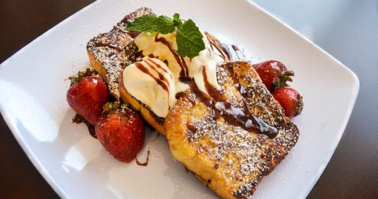 French Toast served on Strawberry Balsamic Gastrique topped with Pecan & Cream Ice Cream, Glazed Strawberries & Mint